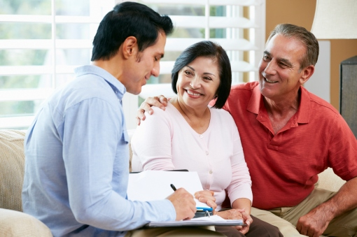 A financial advisor talking to an elderly couple in home