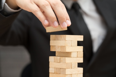 Businessman placing wooden block on a tower. Risk concept